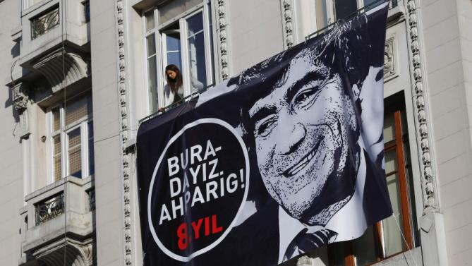 A woman looks out of a window near a banner marking the eighth anniversary of the killing of Turkish-Armenian editor Hrant Dink in Istanbul