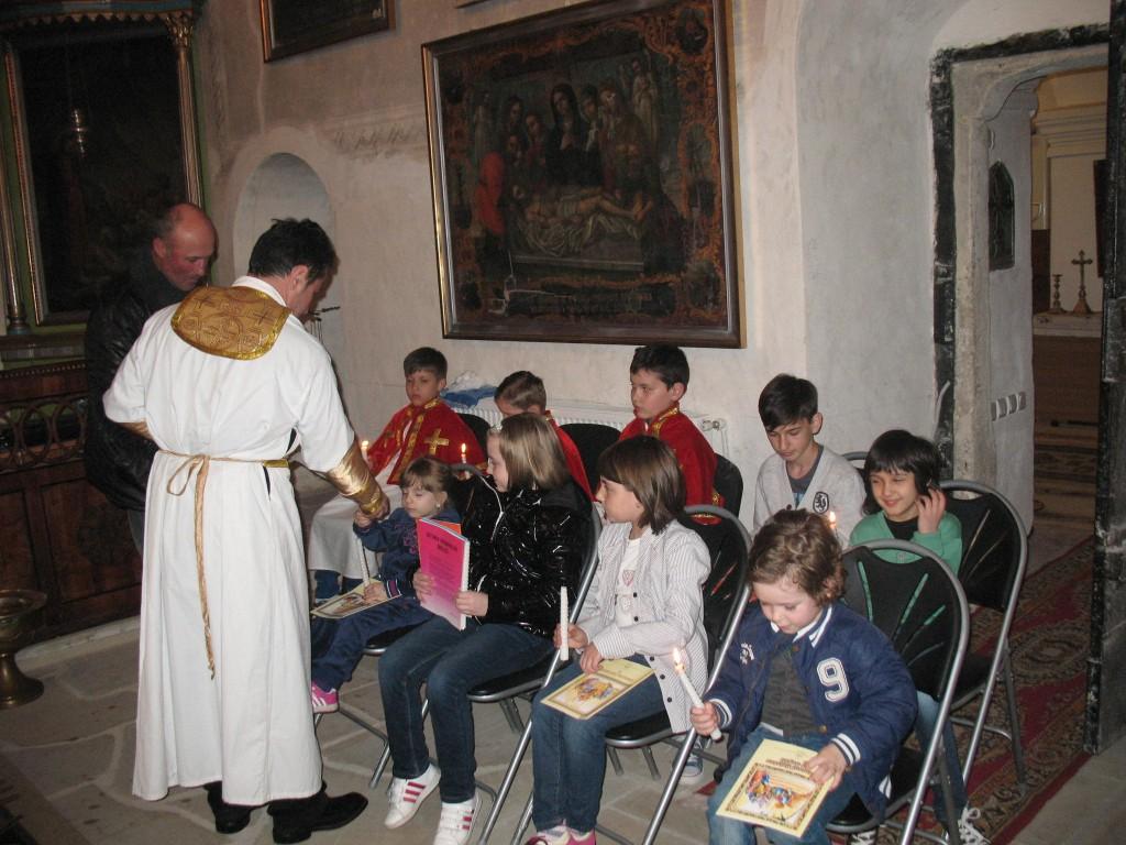 5. Preotul Holca ofera copiilor carti religioase, dupa ritualul spalarii picioarelor