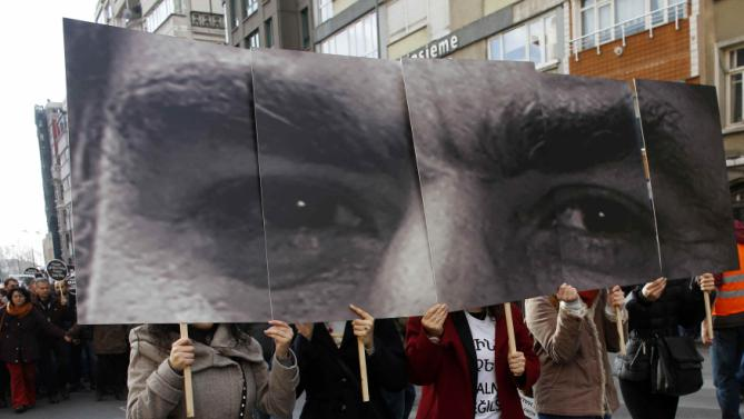 Protesters hold placards showing a close up portrait of Turkish-Armenian editor Hrant Dink during a demonstration to mark the eighth anniversary of his death, in Istanbul